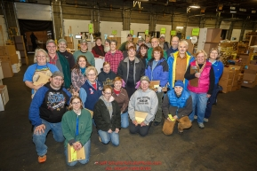 Iditarod volunteers pose for a group photo as they sort and repackage human food and supplies for the trail volunteers to eat at each of the checkpoints on the 2017 Iditarod. The sorting is going on at the Airland Transport warehouse facilities in Anchorage Alaska on Friday  February 17, 2017.Photo by Jeff Schultz/SchultzPhoto.com  (C) 2017  ALL RIGHTS RESVERVED