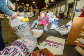Iditarod musher DeeDee Jonrowe repackages some of her drop bags during the musher food drop at Airland Transport warehouse in Anchorage on Wednesday February 18th prior to Iditarod 2015.(C) Jeff Schultz/SchultzPhoto.com - ALL RIGHTS RESERVEDDUPLICATION PROHIBITED WITHOUT PERMISSION