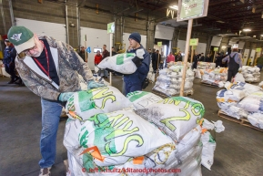 Volunteer John Hooley stacks bags as part of a team of volunteers unload, sort, weigh, tag and palletize thousands of musher food drop bags at Airland Transport warehouse in Anchorage on Wednesday February 18th prior to Iditarod 2015.(C) Jeff Schultz/SchultzPhoto.com - ALL RIGHTS RESERVEDDUPLICATION PROHIBITED WITHOUT PERMISSION