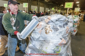 Vounteer Daniel Page shrink-wraps a pallet of musher food bags at Airland Transport warehouse in Anchorage on Wednesday February 18th prior to Iditarod 2015.(C) Jeff Schultz/SchultzPhoto.com - ALL RIGHTS RESERVEDDUPLICATION PROHIBITED WITHOUT PERMISSION