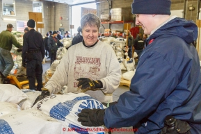 Long-time volunteer Wendy Walters helsp a member of the Alaska Military Youth Academy stack musher food drop bags at Airland Transport warehouse in Anchorage on Wednesday February 18th prior to Iditarod 2015.(C) Jeff Schultz/SchultzPhoto.com - ALL RIGHTS RESERVEDDUPLICATION PROHIBITED WITHOUT PERMISSION