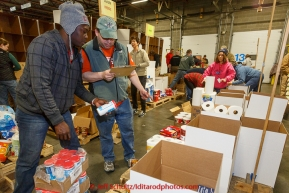 Musher-turned volunteer, Newton Marshall (L) and volunteer Chris Blankenship determine how many coffee creamers they need put on a pallet headed to a particular checkpont.  Volunteers sort, stack and box