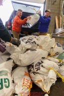 Iditarod musher Linwood Fiedler helps volunteers unload his food drop bags as they sort, weigh, organize and stack the mushers food bags destined for the checkpoints on the 2017 Iditarod at the Airland Transport warehouse facilities in Anchorage Alaska.Wednesday February 15, 2017.Photo by Jeff Schultz/SchultzPhoto.com  (C) 2017  ALL RIGHTS RESVERVED