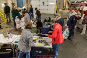 Iditarod volunteers work an assembly line as they unload, weigh, organize and stack the mushers food bags destined for the checkpoints on the 2017 Iditarod at the Airland Transport warehouse facilities in Anchorage Alaska.Wednesday February 15, 2017.Photo by Jeff Schultz/SchultzPhoto.com  (C) 2017  ALL RIGHTS RESVERVED