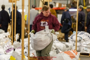 Iditarod volunteers unload, weigh, organize and stack the mushers food bags destined for the checkpoints on the 2017 Iditarod at the Airland Transport warehouse facilities in Anchorage Alaska.Wednesday February 15, 2017.Photo by Jeff Schultz/SchultzPhoto.com  (C) 2017  ALL RIGHTS RESVERVED