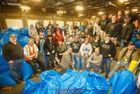 Iditarod volunteers pose for a group photo during the straw bagging day where they unload, bag, stack and shrinkwrap the 1635 bales of straw that is destined for all the checkpoints on the 2017 Iditarod at the Airland Transport warehouse facilities in Anchorage Alaska. Thursday February 9, 2017.Photo by Jeff Schultz/SchultzPhoto.com  (C) 2017  ALL RIGHTS RESVERVED