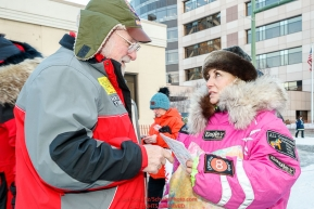 Honorary musher Leo Rasmusson gives a packet of trail mail to DeeDee Jonrowe for her to carry over the trail just prior to the Ceremonial Start of the 2017 Iditarod in Anchorage on Saturday March 4, 2017 Photo by Jeff Schultz/SchultzPhoto.com  (C) 2017  ALL RIGHTS RESVERVED