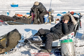 John Baker phones a friend at the checkpoint in Manley Hot Springs as another musher naps on his sled during the 2017 Iditarod on Tuesday March 7, 2017.Photo by Jeff Schultz/SchultzPhoto.com  (C) 2017  ALL RIGHTS RESVERVED