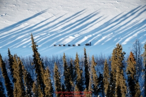A dog team runs through the long shadows of the trees on the Yukon River between Tanana and Ruby during the 2017 Iditarod on Wednesday March 8, 2017.Photo by Jeff Schultz/SchultzPhoto.com  (C) 2017  ALL RIGHTS RESERVED