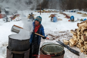 Michelle Phillips gets boiling water from a community cook pot for her dogs at the Takotna checkpoint during Iditarod 2016.  Alaska.  March 09, 2016.  Photo by Jeff Schultz (C) 2016  ALL RIGHTS RESERVED