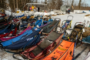 Musher's replacement sleds wait for their owners at the McGrath checkpoint during Iditarod 2016.  Alaska.  March 09, 2016.  Photo by Jeff Schultz (C) 2016  ALL RIGHTS RESERVED