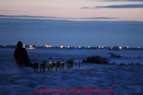 Cim Smyth runs on the trail with the lights of the  Unalakleet checkpoint in back ground on his way in on Sunday March 10, 2013.