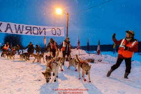 Volunteers lead Ed Stielstra dogs to the line at the Takotna checkpoint after his 24-hour layover in the early morning on Thursday March 10 during Iditarod 2016.  Alaska.    Photo by Jeff Schultz (C) 2016  ALL RIGHTS RESERVED