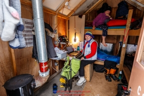 Volunteer comms Katy Kerris (on bunk) and Valerie Saiki inside the comms shack at the Ophir Checkpoint on Thursday March 10 during Iditarod 2016.  Alaska.    Photo by Jeff Schultz (C) 2016  ALL RIGHTS RESERVED