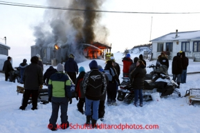People watch as firefighters try to put out a house fire in the village of Elim on Monday March 11, 2013.Iditarod Sled Dog Race 2013Photo by Jeff Schultz copyright 2013 DO NOT REPRODUCE WITHOUT PERMISSION