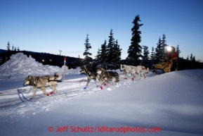 Mitch Seavey heads out of the Elim checkpoint with his headlamp on at dusk on Monday March 11, 2013.Iditarod Sled Dog Race 2013Photo by Jeff Schultz copyright 2013 DO NOT REPRODUCE WITHOUT PERMISSION