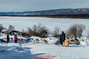 Wade Marrs runs down the road as he leave the Ruby checkpoint with the Yukon River in the background on Friday March 11 during Iditarod 2016.  Alaska.    Photo by Jeff Schultz (C) 2016  ALL RIGHTS RESERVED