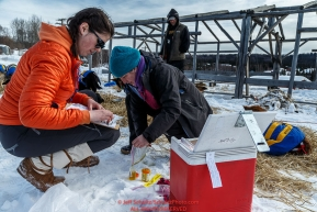P-Team members Grace Bolt (Left) and Leoni Ballard collect urine samples from Hugh Neff's team at the Ruby Checkpoint during the 2016 Iditarod.  March 11, 2016   Photo by Jeff Schultz (C) 2016  ALL RIGHTS RESERVED