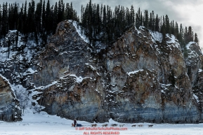 Michelle Phillips and team run along the rock cliffs shortly after leaving the Ruby Checkpoint during the 2016 Iditarod.  March 11, 2016    Photo by Jeff Schultz (C) 2016  ALL RIGHTS RESERVED
