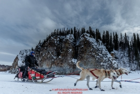 Paul Gebhardt's team runs past cliffs shortly after leaving the Ruby Checkpoint during the 2016 Iditarod.  March 11, 2016   Photo by Jeff Schultz (C) 2016  ALL RIGHTS RESERVED