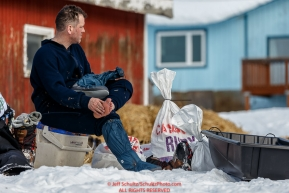 Jason Campeau dries his feet at the Ruby Checkpoint during the 2016 Iditarod.  March 11, 2016    Photo by Jeff Schultz (C) 2016  ALL RIGHTS RESERVED