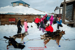 School kids sit on a snow berm at the Kaltag checkpoint and watch Mitch Seavey's dogs during the 2017 Iditarod on Saturday afternoon March 11, 2017.Photo by Jeff Schultz/SchultzPhoto.com  (C) 2017  ALL RIGHTS RESERVED