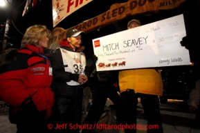 Mitch Seavey, left, 53, with his wife Janine, accepts the winner's check from Greg Deal of Wells Fargo, after pulling into Nome first and winning his second Iditarod sled dog race on Tuesday March 12, 2013. Seavey made the journey from Willow in 9 days, 7 hours, 39 minutes, 56 seconds. Iditarod Sled Dog Race 2013Photo by Jeff Schultz copyright 2013 DO NOT REPRODUCE WITHOUT PERMISSION