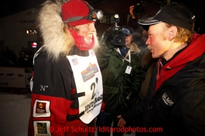 Aily Zirkle, left, greets with Iditarod winner Mitch Seavey after she pulled into Nome minutes after him on Tuesday March 12, 2013.Iditarod Sled Dog Race 2013Photo by Jeff Schultz copyright 2013 DO NOT REPRODUCE WITHOUT PERMISSION