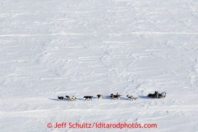 Martin Buser kicks back on his sled with his foot up as he travels over Golovin Bay on the way to the White Mountain checkpoint on Tuesday March 12, 2013.Iditarod Sled Dog Race 2013Photo by Jeff Schultz copyright 2013 DO NOT REPRODUCE WITHOUT PERMISSION