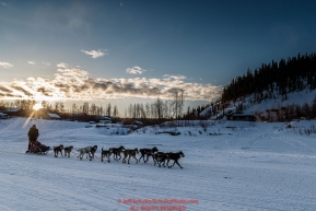 Anna Berington runs down the Yukon River as she leaves the Ruby Checkpoint at sunrise on Saturday March 12th during the 2016 Iditarod.  Alaska    Photo by Jeff Schultz (C) 2016  ALL RIGHTS RESERVED