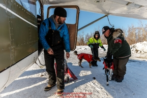 Pilot O.E. Robbins is ready to load the dropped dogs vet Roger Troutman and pilot Daniel Hayden are bringing his way at the Ruby Checkpoint on Saturday March 12th during the 2016 Iditarod.  Alaska    Photo by Jeff Schultz (C) 2016  ALL RIGHTS RESERVED