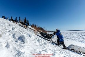 Paige Drobny runs up the steep river bank from the Yukon River to the Galena checkpoint on Saturday March 12th during the 2016 Iditarod.  Alaska    Photo by Jeff Schultz (C) 2016  ALL RIGHTS RESERVED