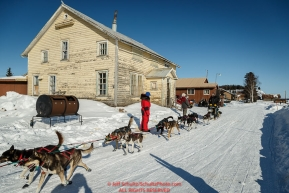 Nathan Schroeder runs down the road into the Nulato checkpoint past an old convent, turned thrift store, on Saturday afternoon March 12th during the 2016 Iditarod.  Alaska    Photo by Jeff Schultz (C) 2016  ALL RIGHTS RESERVED
