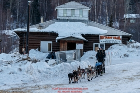 Kristy Berington runs past the Community Hall as she leaves the Ruby Checkpoint in the morning on Saturday March 12th during the 2016 Iditarod.  Alaska    Photo by Jeff Schultz (C) 2016  ALL RIGHTS RESERVED