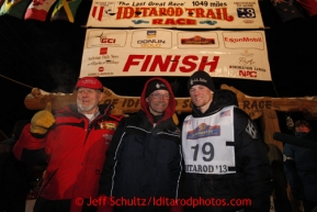 Three generations of Seavey's Dan, Mitch and Dallas pose at the finish line in Nome shorlty after Dallas crossed the finish line in 4th place on Wednesday March 13, 2013. Iditarod Sled Dog Race 2013Photo by Jeff Schultz copyright 2013 DO NOT REPRODUCE WITHOUT PERMISSION