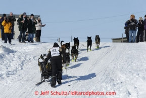 Brent Sass is welcomed to Nome by race fans as he runs up the seawall ramp from the Bering Sea onto Nome's Front Street less than a mile from the finish line in Nome on Wednesday March 13, 2013. Iditarod Sled Dog Race 2013Photo by Jeff Schultz copyright 2013 DO NOT REPRODUCE WITHOUT PERMISSION