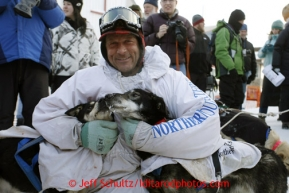 Martin Buser hugs his lead dogs, litter-mates Flash and Quick, at the finish line in Nome on Wednesday March 13, 2013. Iditarod Sled Dog Race 2013Photo by Jeff Schultz copyright 2013 DO NOT REPRODUCE WITHOUT PERMISSION