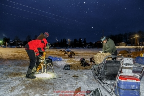 Volunteer veterinarians Scott Rosenbloom and Bruce Pedersen are given a dropped dog from Geir Idar Hjelvik in the early morning at the Kaltag checkpoint on Sunday March 13th during the 2016 Iditarod.  Alaska    Photo by Jeff Schultz (C) 2016  ALL RIGHTS RESERVED