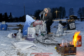 Lars Monsen prepares to cook dog food in the early morning at the Kaltag checkpoint on Sunday March 13th during the 2016 Iditarod.  Alaska    Photo by Jeff Schultz (C) 2016  ALL RIGHTS RESERVED