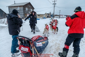 Ed Stielstra brings his food bag to his sled as he checks in and out of  the Kaltag checkpoint on Sunday morning March 13th during the 2016 Iditarod.  Alaska    Photo by Jeff Schultz (C) 2016  ALL RIGHTS RESERVED