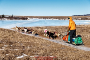 Kelly Maixner runs on an ice and dirt trail a few miles before the Unalakleet checkpoint on Sunday March 13th during the 2016 Iditarod.  Alaska    Photo by Jeff Schultz (C) 2016  ALL RIGHTS RESERVED