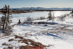Kelly Maixner runs on an ice and dirt trail off a lagoon a few miles before the Unalakleet checkpoint on Sunday March 13th during the 2016 Iditarod.  Alaska    Photo by Jeff Schultz (C) 2016  ALL RIGHTS RESERVED
