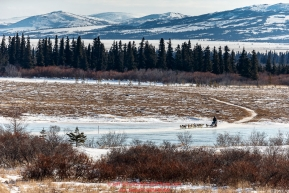 Richie Diehl runs across a lagoon with the Whaleback Mountains in the background a few miles before the Unalakleet checkpoint on Sunday March 13th during the 2016 Iditarod.  Alaska    Photo by Jeff Schultz (C) 2016  ALL RIGHTS RESERVED