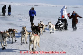 Justin Savidas gets a soda handed to him as he crosses the Nome road about 4 miles from the finish line in 30 mph winds on Thursday March 14, 2013 during the Iditarod Sled Dog Race 2013Photo by Jeff Schultz copyright 2013 DO NOT REPRODUCE WITHOUT PERMISSION