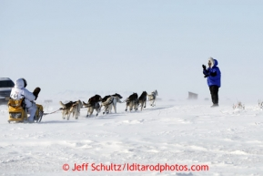 Matt Giblin waves to Donlin Gold representative Sue Gamache as he crosses the Nome road a few miles from Nome in 30 mph winds on Thursday March 14, 2013 during the Iditarod Sled Dog Race 2013Photo by Jeff Schultz copyright 2013 DO NOT REPRODUCE WITHOUT PERMISSION