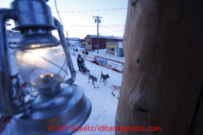 The Widows Lamp, lit until the last musher reaches Nome hangs from the burled finish line arch in as Paige Drobny runs down the finish line in 34th place on Thursday March 14, 2013. Iditarod Sled Dog Race 2013Photo by Jeff Schultz copyright 2013 DO NOT REPRODUCE WITHOUT PERMISSION
