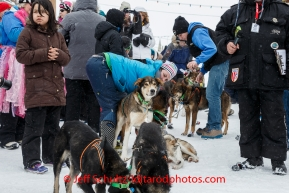 A crowd gathers around Newton Marshall and team in the finish chute after he arrived in 43rd place in Nome on Friday March 14 during the 2014 Iditarod Sled Dog Race.PHOTO (c) BY JEFF SCHULTZ/IditarodPhotos.com -- REPRODUCTION PROHIBITED WITHOUT PERMISSION