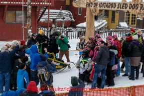 A crowd of K-9 Fairies gathers around Newton Marshall for a group photo in the finish chute after he arrived in 43rd place in Nome on Friday March 14 during the 2014 Iditarod Sled Dog Race.PHOTO (c) BY JEFF SCHULTZ/IditarodPhotos.com -- REPRODUCTION PROHIBITED WITHOUT PERMISSION