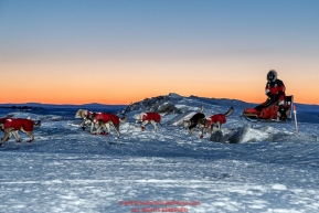 Paul Gebhardt runs over sea ice at dawn as he approaches the Koyuk checkpoint on Monday March 14th during the 2016 Iditarod.  Alaska    Photo by Jeff Schultz (C) 2016  ALL RIGHTS RESERVED