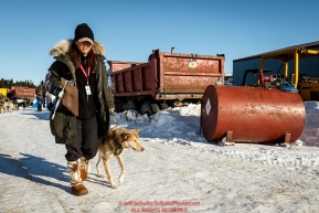 Volunteer Vet Justine Lee walks a dropped dog at the Elim checkpoint on Monday March 14th during the 2016 Iditarod.  Alaska    Photo by Jeff Schultz (C) 2016  ALL RIGHTS RESERVED